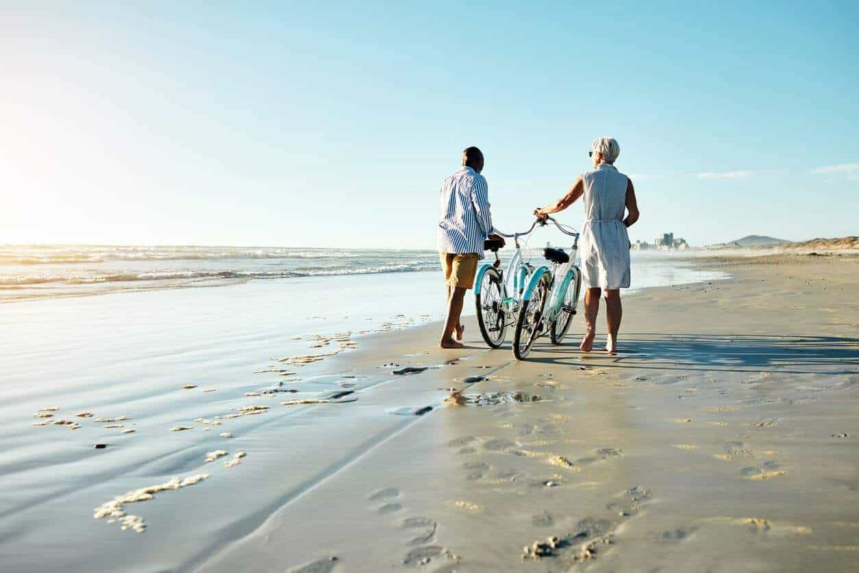 Two people walking with bikes on beach discussing their small business retirement plan